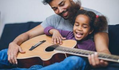 Father and daughter playing a guitar on the couch