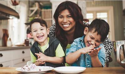 Mother and two sons sitting at the kitchen table and laughing