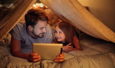 An adult reads to a child from a tablet screen under a tent indoors.