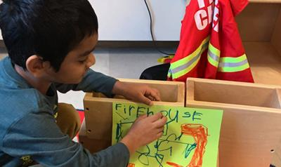 A young boy in a classroom taping an image to block.