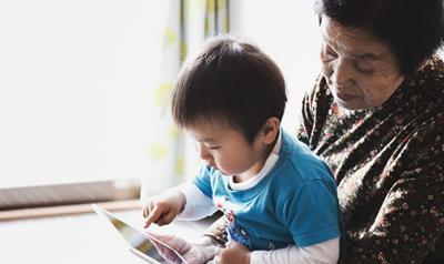 Preschool boy in his grandma's lap, learning on a tablet