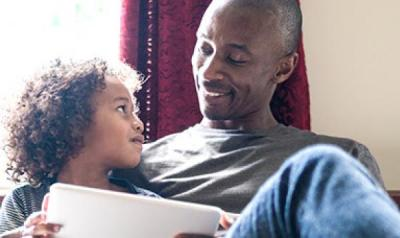 father and son with ipad smiling