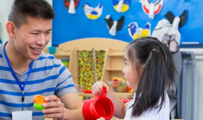 Child and teacher playing with toys in classroom