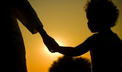 A child and a family member in silhouette against a setting sun.