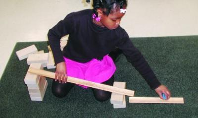 A young child builds a ramp with blocks