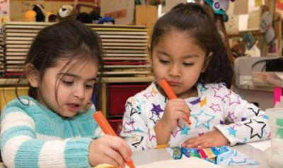 Two young children draw with markers