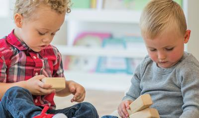 Two toddlers playing with blocks