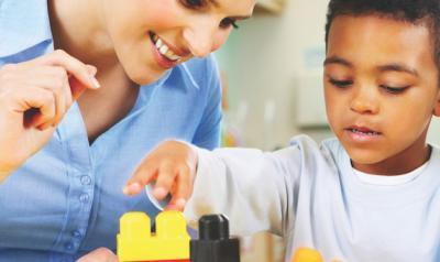 Teacher observing student build blocks
