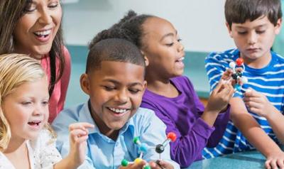 Teacher in a classroom with 4 diverse children