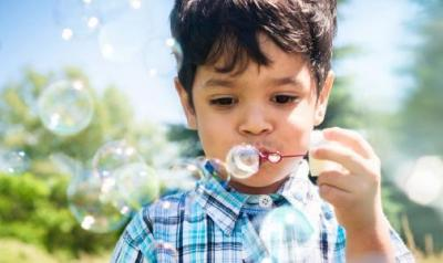 Preschool aged boy blowing bubbles outside