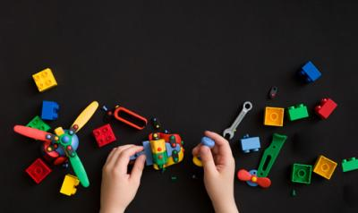 a child's hands playing with assorted toys