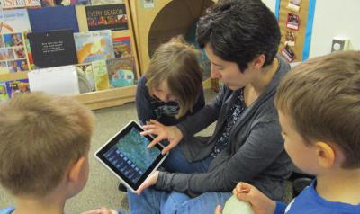 a teacher showing children a game on an ipad
