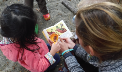 a teacher showing a child a nature book outside