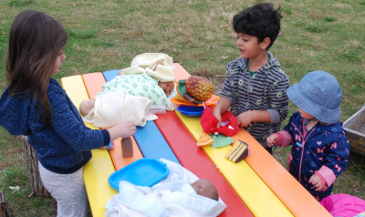 children at an outdoor table with toys