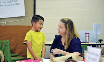 Teacher and student working with materials