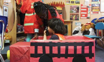 Child pretending to be a firefighter in a cardboard firetruck