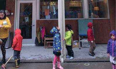 Children standing outside in rain