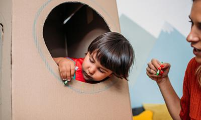student playing in a cardboard fort with teacher