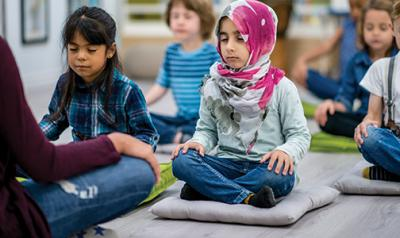 Students sits on mats and do meditation exercises with a teacher