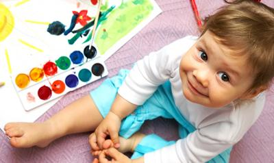 Toddler sitting next to a painting kit