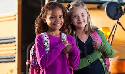 Two girls standing next to a school bus