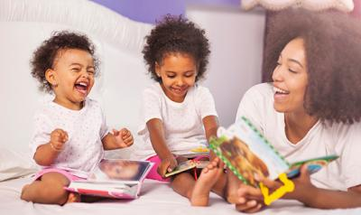 Mother reading with toddler girls