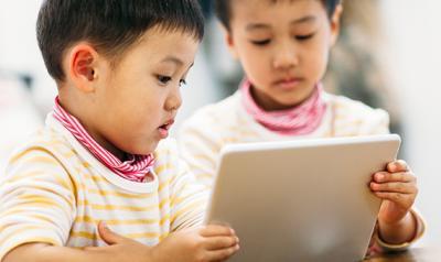 Two siblings watching tablet