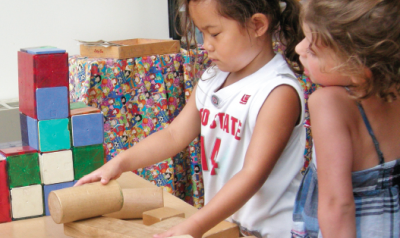 Two girls playing with blocks in classroom