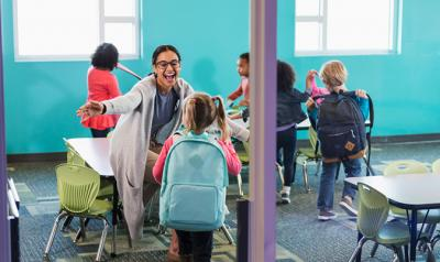 A teacher welcoming her students into the classroom.