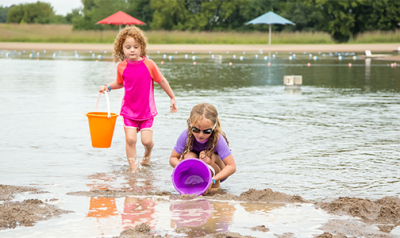 Two young girls at the lake scooping water into buckets