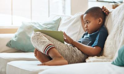 young preschool boy sitting on a couch reading