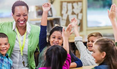 Educator playfully raising hand with children