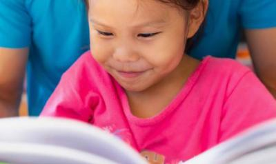 A young child reading a book.