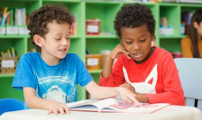 young children reading a book.
