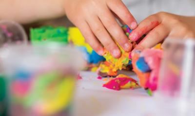 child's hands kneading playdough