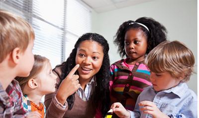 Preschool teacher in a classroom with a group of preschool children