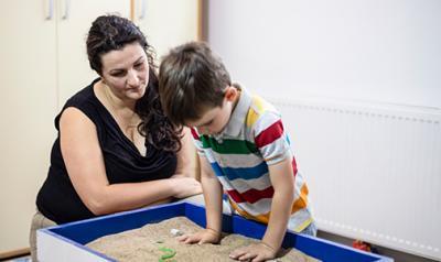 Teacher watching a young boy play in a sandbox