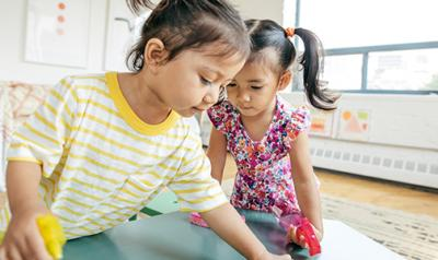 Two preschool girls playing in the classroom