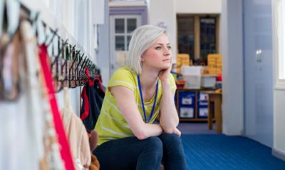Teacher sitting in a hallway, thinking