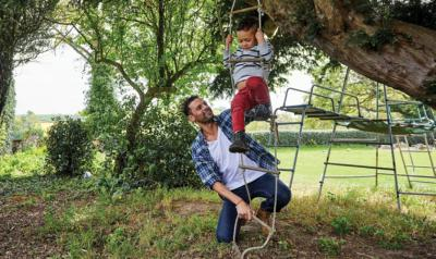 father and son playing on rope swing outside