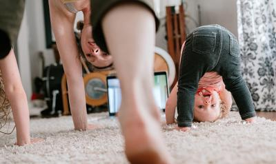 mother and two young girls doing yoga in the living room