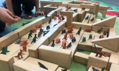 Children play with blocks and dinosaur figurines.
