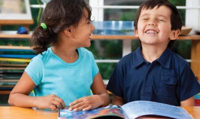 Two children enjoying reading a book.