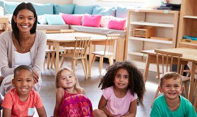 Group of diverse children sitting in classroom.