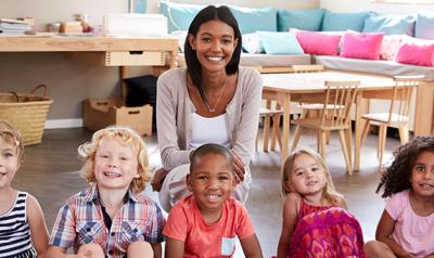 Group photo of teacher smiling with preschool students in classroom