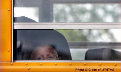 Little boy looking outside of school bus window