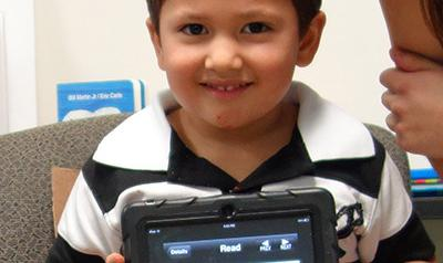 Child showing his artwork on a tablet.