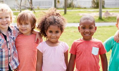 Diverse set of children smiling and hugging
