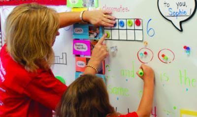 A teacher helps a child develop math concepts