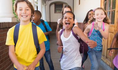 A group of primary aged children running down a hallway